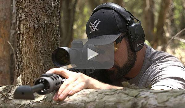 Josh Froelich kneeling behind a large fallen tree trunk