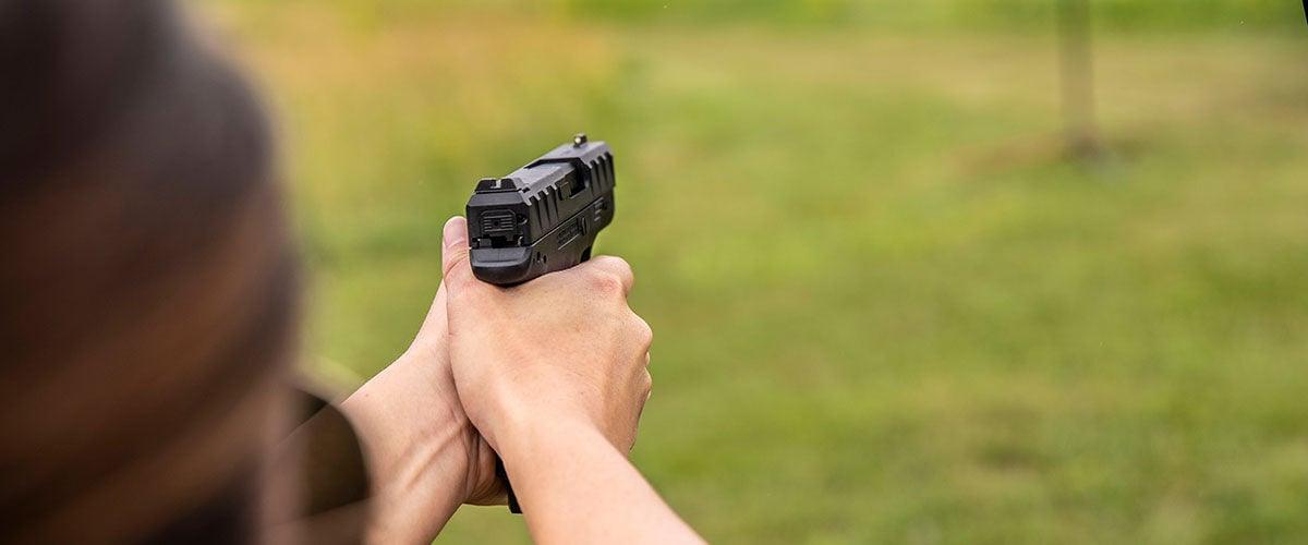 Person shooting handgun at an outdoor range