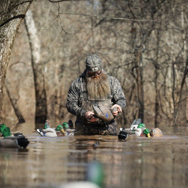 Dennis Loosier wading in water with decoys