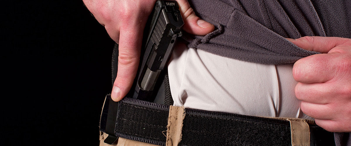 Person putting pistol in concealed holster