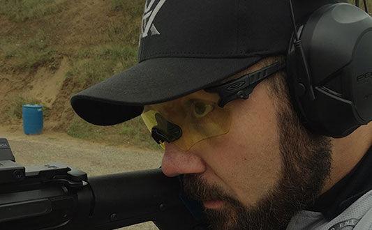 Josh Froelich looking down rifle scope