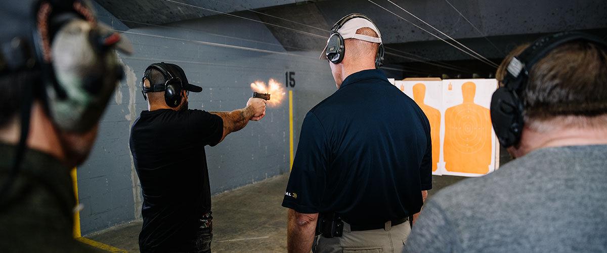 people at an indoor gun range training