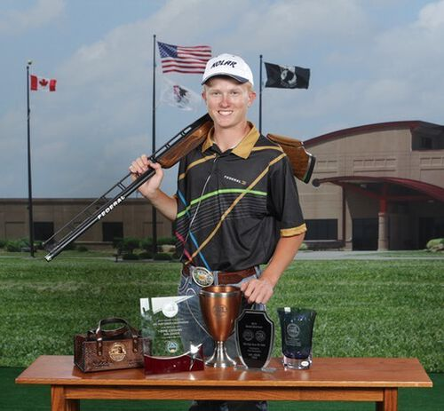 Grayson Stuart with his shotgun standing in front of a trophy
