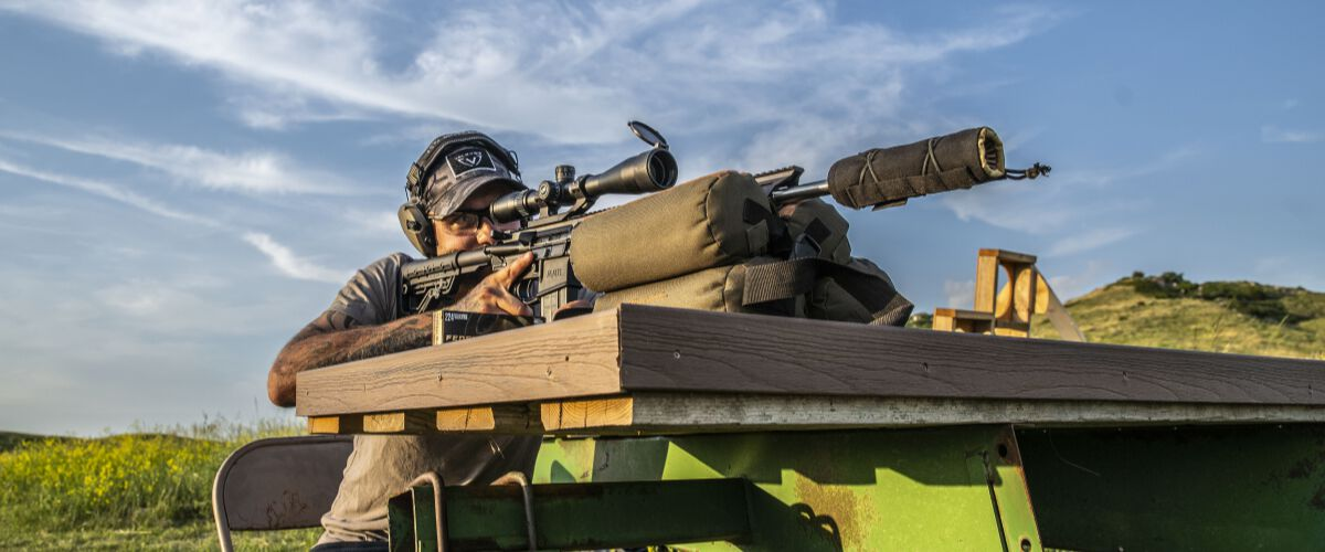 man looking down the scope of a rifle resting on a table