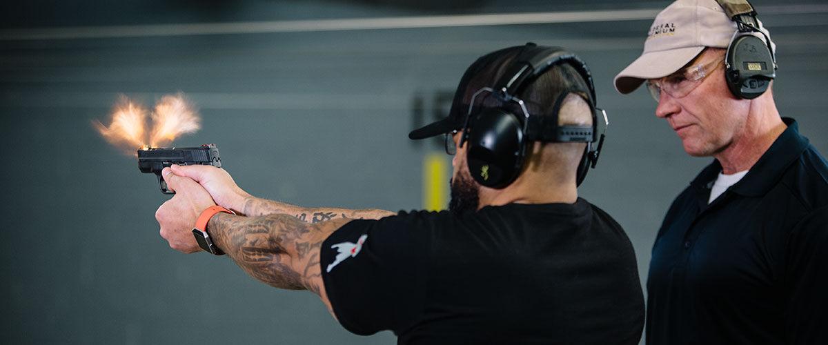 One person watching another shoot a handgun at an indoor gun range