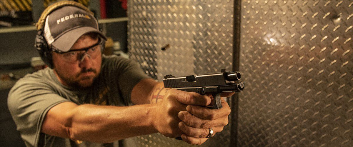 Man shooting a handgun at an indoor range