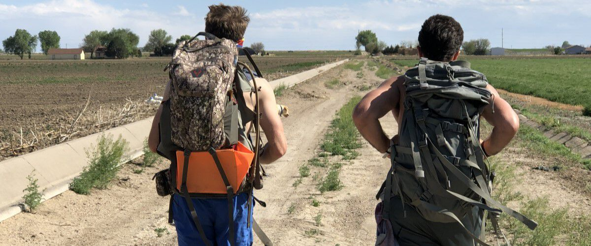 two men carring backpacks on a dirt road