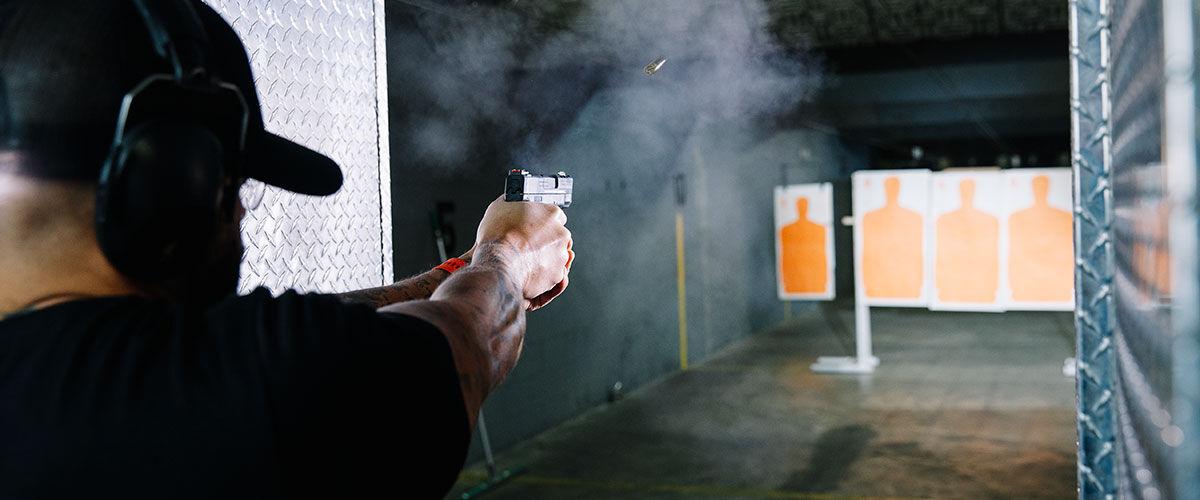Man shooting pistol at orange target