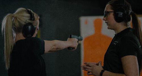woman shooting a handgun at an indoor range