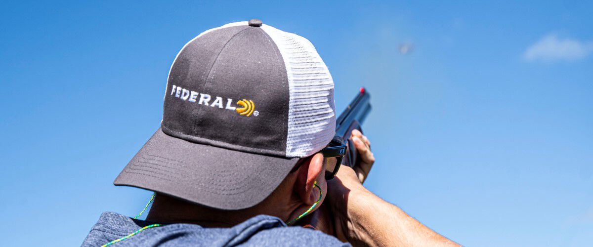 man shooting with a Federal trucker hat on