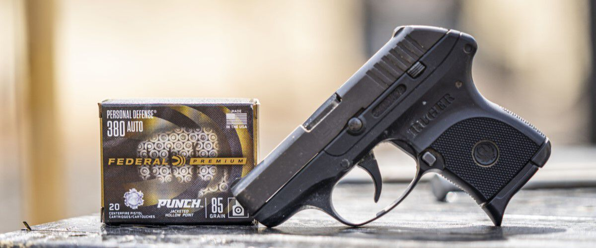 Handgun on a table with a box of Federal Premium Punch