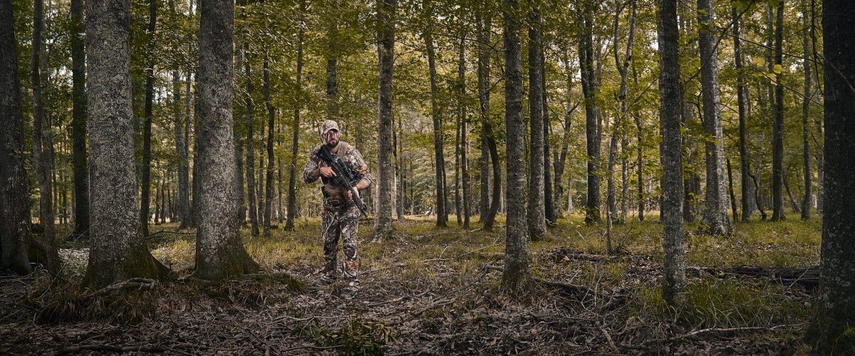 Kip walking through a wooded area with his rifle