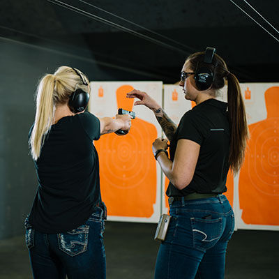 Two Women at an Indoor Gun Range