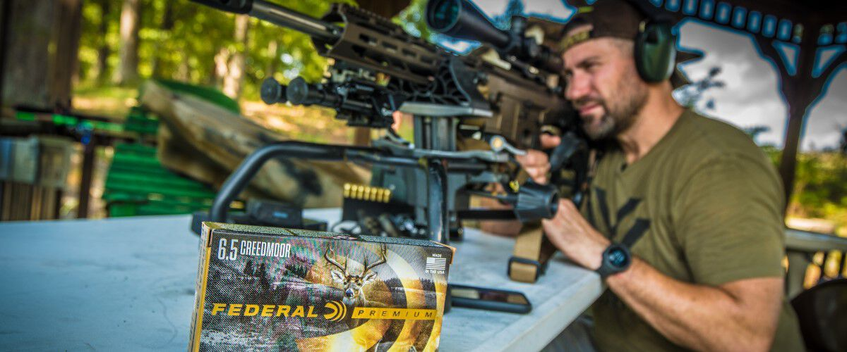 Kip looking down a rifle scope with a box of Federal Premium Nosler Accubond sitting beside him