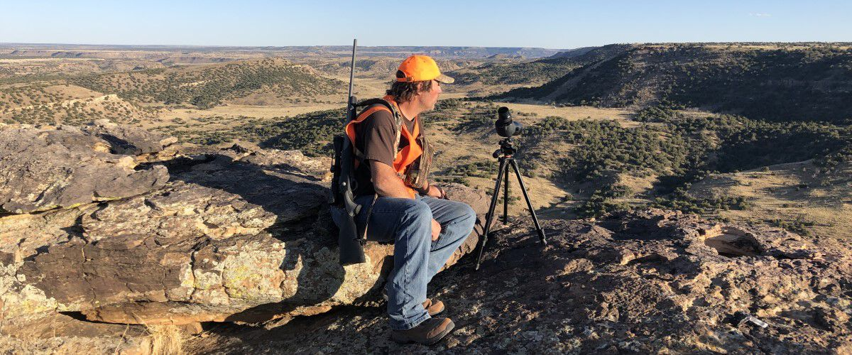 Hunter sitting near a cliff with a range finder looking for deer on the prairie