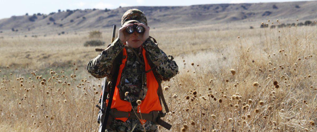 Hunter looking through binoculars on the prairie
