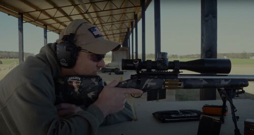 Jim Gilliland looking down the scope of a rifle