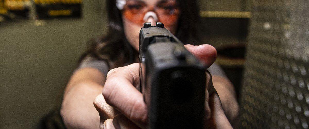 Woman pointing a handgun at the camera