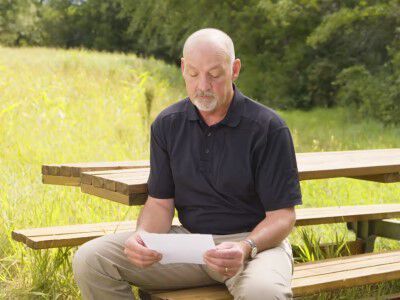 man sitting outside reading a letter