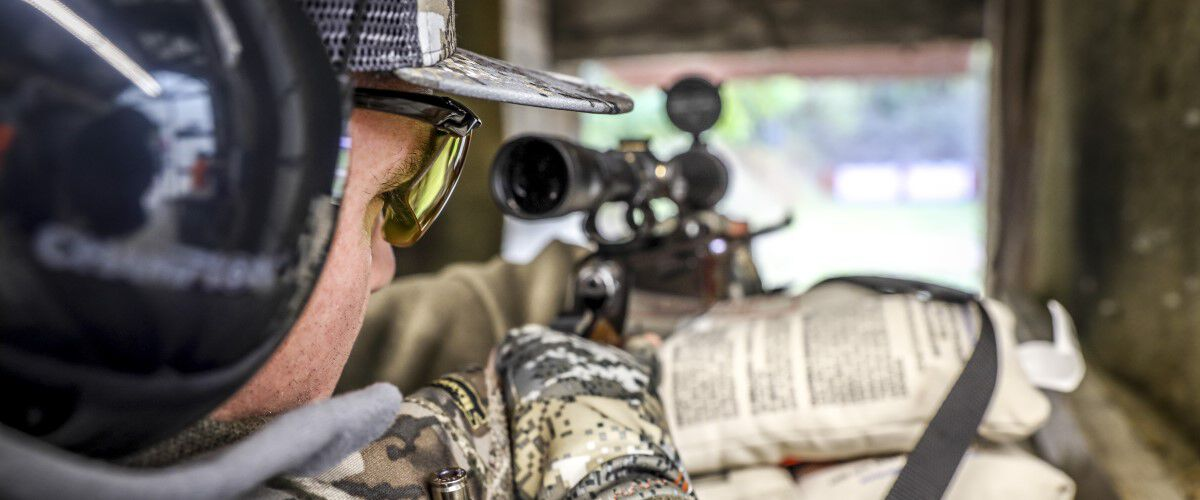 man looking down rifle scope at outdoor range