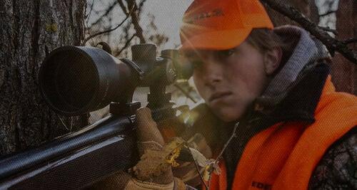 Lady shooting a rifle outside