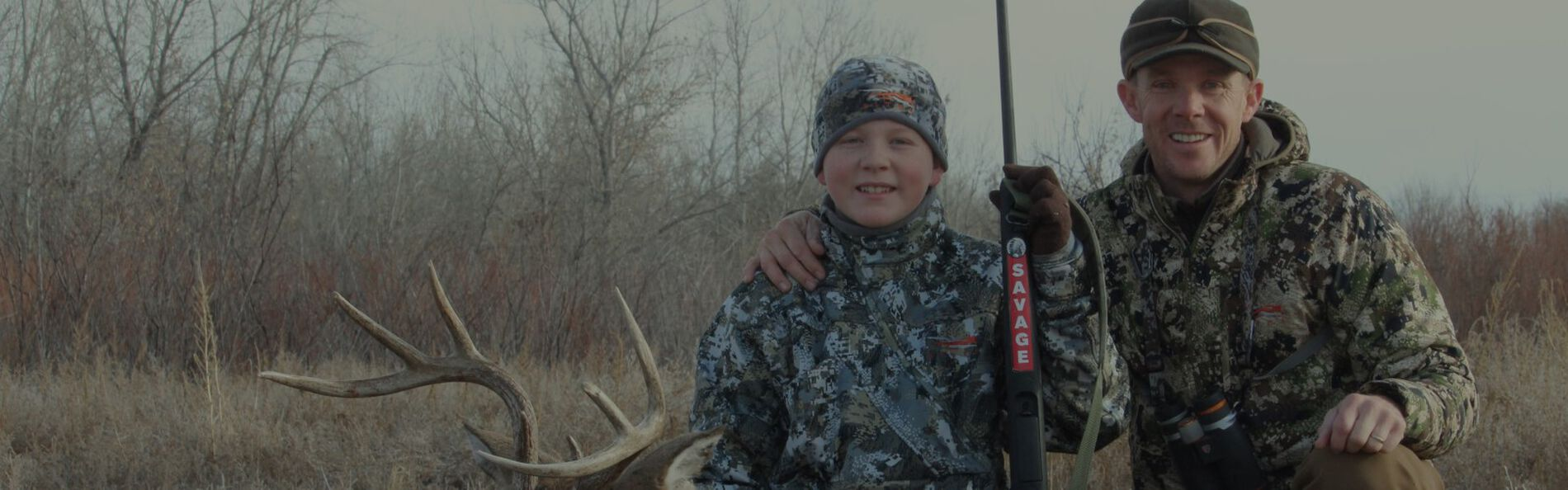 Young hunter kneeling beside a dead deer with an adult hunter
