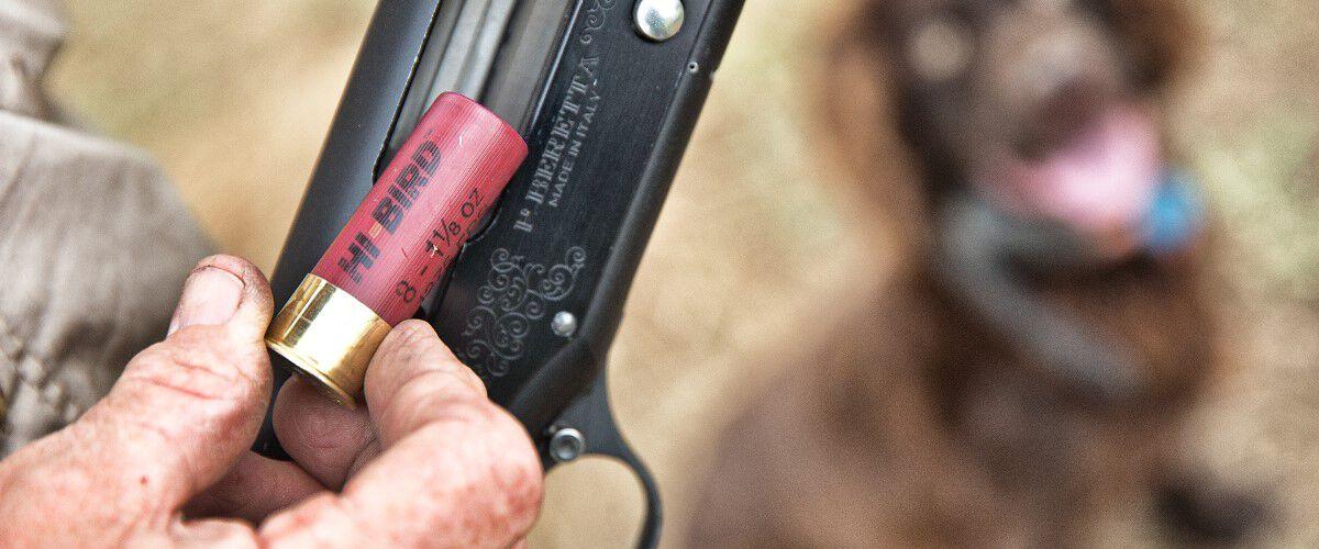 shotshell being loaded into shotgun