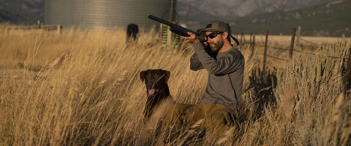 hunting dog sitting next to hunter who is aiming shotgun
