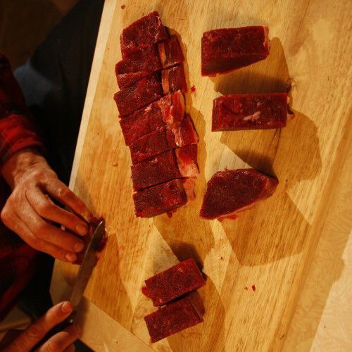 deer tenderloin being trimmed of fat and connective tissue