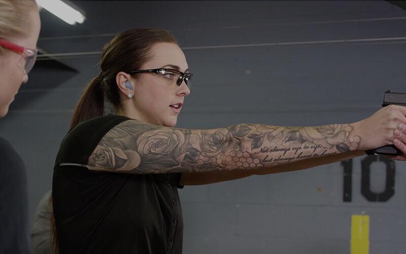 Women at in-door gun range holding a pistol