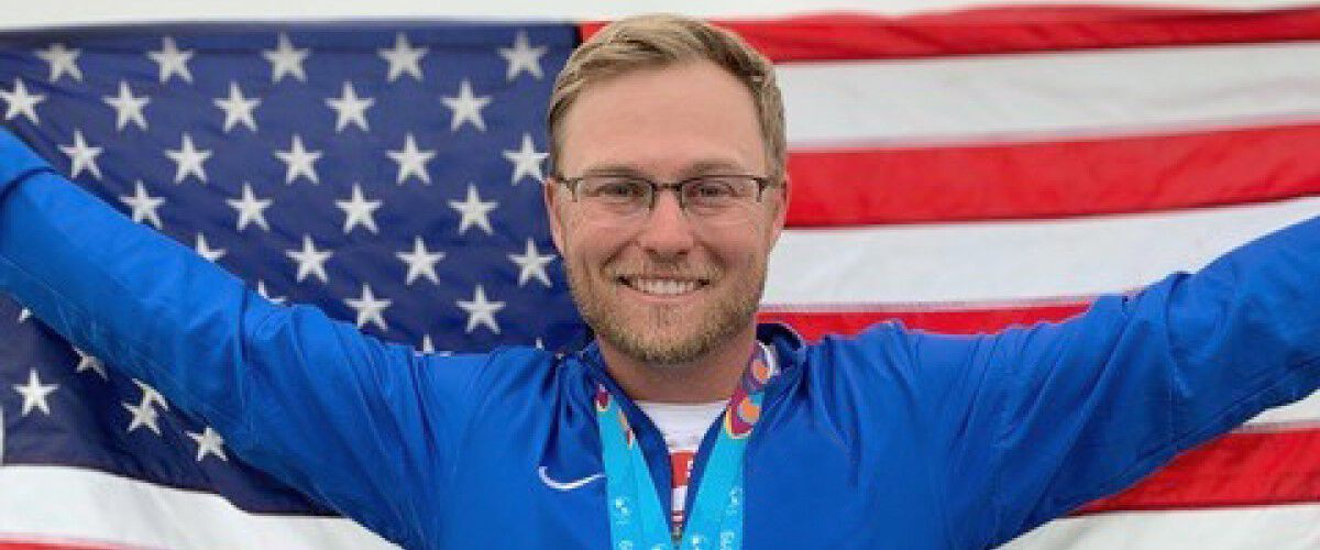 Brian Burrows standing in front of the American flag