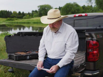 man sitting on a truck bed reading a letter