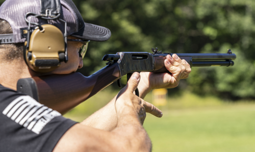 Man looking down the sights of a lever action rifle