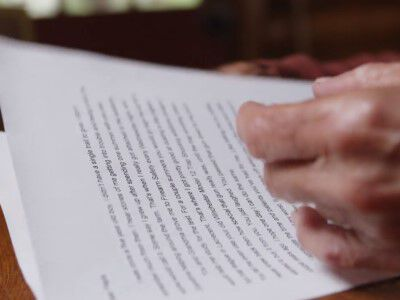 wrinkled hands on a typed letter