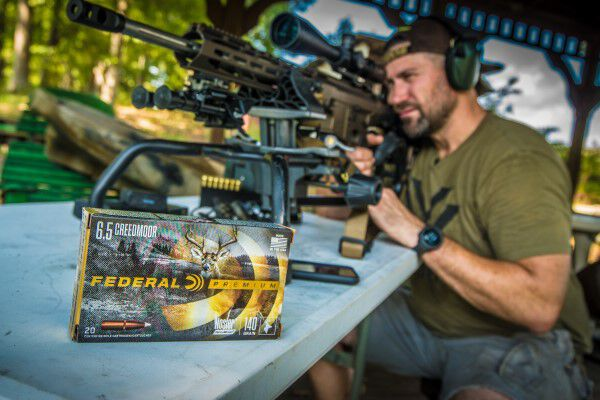 Kip Campbell looking down a rifle scope with a box of Federal Premium Nosler Accubond beside him