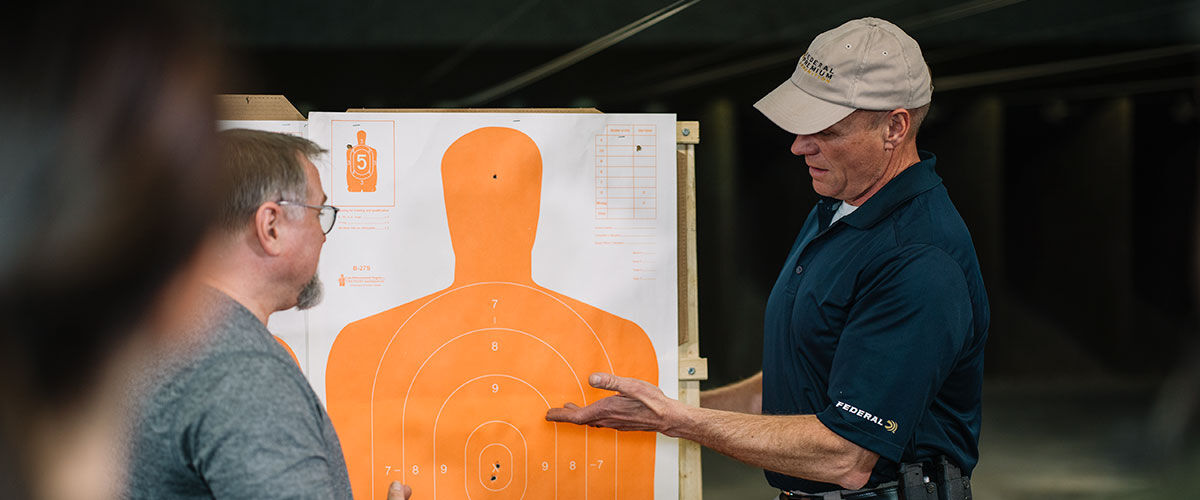 A person talking to others at an indoor gunrange