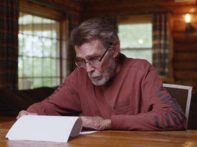 man sitting inside reading a letter